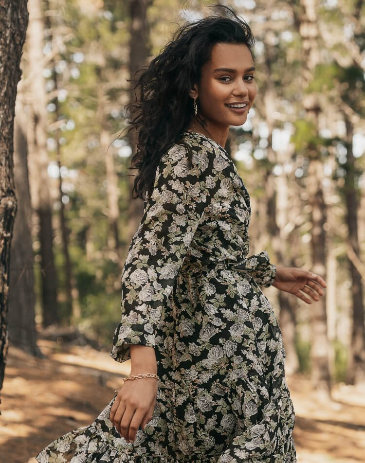 Young woman walking among trees